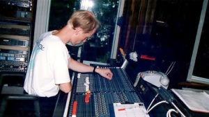 Man med blont här och vit T-skjorta står vid mixerbord i musikstudio.