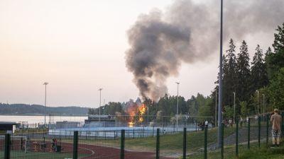 Ett hus brinner i bakgrunden och en rökpelare stiger mot skyn. I förgrunden en sportplan och hockeyrink.