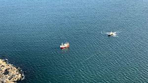 En flygbild av en rödvit trålare som råkat i sjönöd och driver mot grynnor. Sjöbevakningens båt närmar sig.
