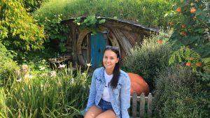 Jane istuu Hobbiton-kylän kuavuspaikalla mökin edessä.