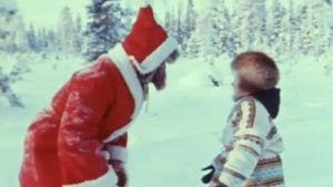 Joulupukki ja lapsi lumisessa maisemassa