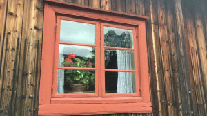 En röd blomma i ett fönster med röda bågar i ett gammalt hus