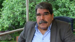 Salih Muhammad är man med stor mustasch och glasögon. På bilden är han klädd i kostym.