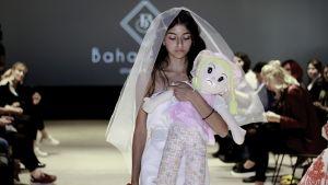 Rauan Badawieh en klänning designad av Bahaulddin Rawi. Modellen går på catwalken och håller en docka i famnen.