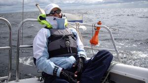 Tuhkimotarinoiden Ulla istuu purjeveneen sitloodassa.