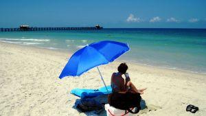 nainen rannalla ottamassa aurinkoa