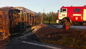 En nerbrunnen buss ligger på vägen med en brandbil bredvid sig. Minst 14 personer dog i en bussolycka i Tatarstan i Ryssland den 2 juli 2017.