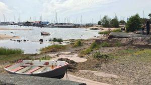 En klippig strand med båtar i bakgrunden.