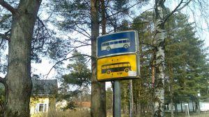 Trafikmärken för en busshållplats. En väg och ett hus i bakgrunden.