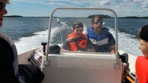 Rasmus Lundén, projektkoordinator vid Icehearts svenskspråkiga verksamhet uten och åker båt med barnen.