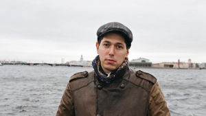 En man står vid strandkanten och bakom honom syns hav.