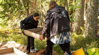 Två personer sållar jord på en arkeologisk utgrävning.