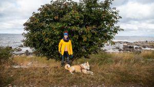Nainen ja koira saaristossa pihlajan edessä.