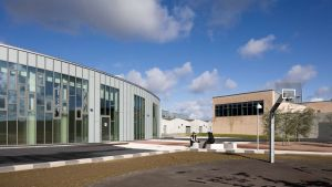 vy över Storstrøm fängelse med en byggnad med stora glasfönster och en uteplats med en basketring
