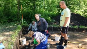 Vantaan Jokiniemen yleisökaivauksille osallistujat kaapivat maata, arkeologian opiskelija katselee
