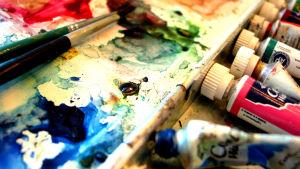 Konstnärsmaterial: Färgtuber, penslar.