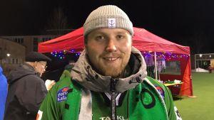 En man i grön jacka står utomhus på ett sportevenemang. Han ler och tittar in i kameran.