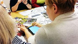 Ryhmä naisia (anonyymi) testaa älypuhelinsovelluksen käyttöä
