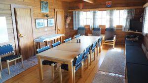 Ett matbord med åtta stolar i trä med blått tyg från 1970-talet i en stor representationssommarstuga.