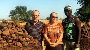 Teoksen ohjaaja ja käsikirjoittaja paikallisen kanssa iloisina kuumaa savannia aitaavan muurin edessä