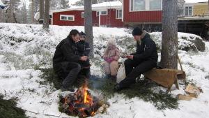 Daniel Eriksson med sina barn och sin svägerska, grillar korv på baksidan av huset