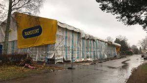 En byggnad som saneras och som är intäkt i ett stort tält.