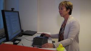 Kvinna i kort hår står vid sitt arbetsbord och tittar på dataskärmen