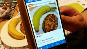 kännykkäruudulla kuva välipalasta, banaani ja karjalanpiirakka