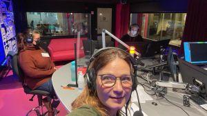 Kolme naista radiostudiossa joista selfien ottanut katsoo kameraan.