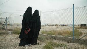 Två kvinnor iklädda heltäckande niqabs står vid ett nätstängsel på IS-lägret. En av kvinnorna har en röd keps i handen.