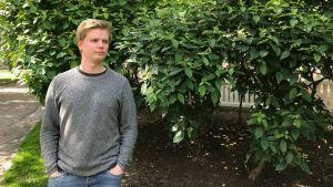 En man iklädd en grå tröja och jeans. Står med händerna i fickorna, framdför ett träd med gröna löv. Han tittar åt sidan.