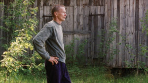 Verryttelyasuun pukeutunut Veijo Rönkkönen tähyilee kaukaisuuteen korkean ruohikon keskellä. Taustalla harmaantunut, sammalkattoinen lato.