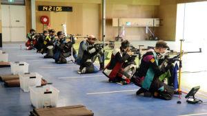 Flera skyttar skjuter knästående mot tavlor.