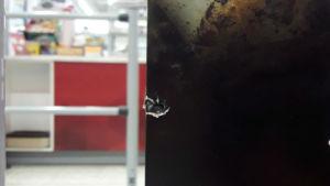 Ett kulhål i en reklamskylt efter ett skott i matbutik.