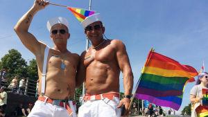 Vesa Uusitalo och Aleksi Tiiro klädda i sjömansmössor, vita byxor och bar överkropp på Helsingfors pride 2016.