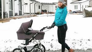 nainen työntää lumisessa pihapiirissä vauvanvaunuja