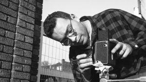 Valokuvaaja Harold Feinstein säätää kameraansa kadulla New Yorkissa