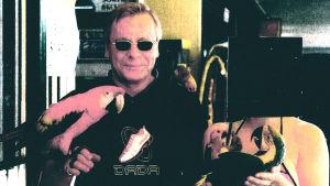Raimo Andersson med papegoja på handen.