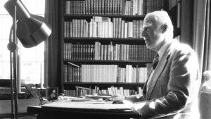 Georg Henrik von Wright sitter vid sitt skrivbord.