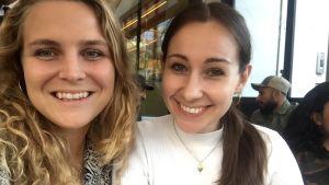 Två kvinnor sitter på ett kafé. Den ena har blont lockigt hår och den andra brunt. rakt hår. De ler stort.