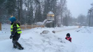 kaksi lasta leikkii lumihangessa