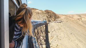 En kvinna åker tåg. Hon lutar sig ut genom fönstret och tittar bakåt mot de andra tågvagnarna. Tåget åker över en bro i ett berg.