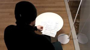 Man som sitter vid bord med räkning från indrivningsbyrå framför sig.