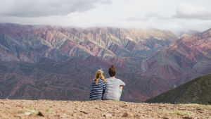 En kvinna och en man sitter på ett berg och blickar ut över en vacker bergskedja som skiftar i rött och grönt.