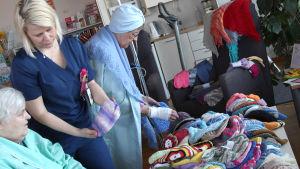 Två damer och en sjukvårdare väljer ut cancermössor