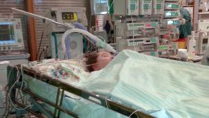 Ett barn ligger och sover i en sjukhussäng. Hon har en massa slangar och sladdar kopplade till sig.