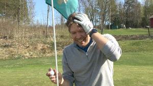 Jere Jaakkola, en man med grå tröja, håller sig om huvudet då han just slagit två hole-in-one. Han står bredvid en flagga vid hålet.