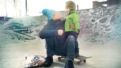 En pappa håller om sin pojke vid en skejtramp.