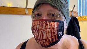 Taina West talviuimarikamppeissa, Teeman elokuvafestivaalin maski kasvoilla ja pipo päässä.