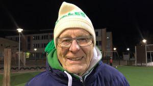 En äldre man står utomhus framför en idrottsplan. Han har på sig en mössa som det står Akilles på.